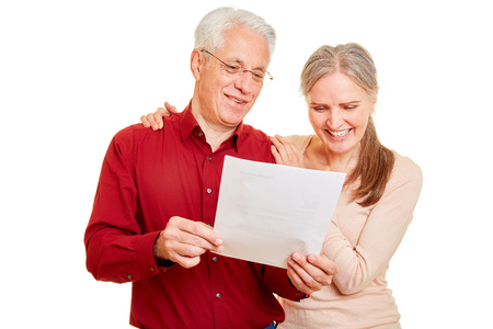 Smiling couple seniors together reads good news as a letter Archivio Fotografico