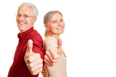 Happy seniors couple keeps thumbs up as a gesture of approval