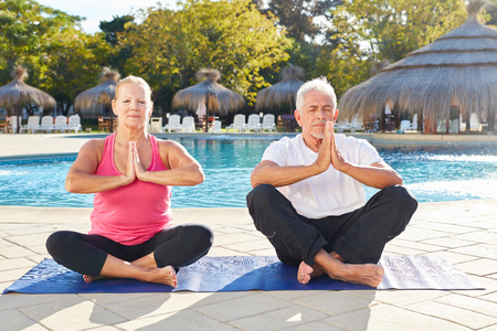 Senior couple sitting by the pool and doing a meditation with clasped hands Stock Photo