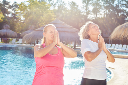 Two women doing yoga meditation together at the pool during a spa vacation