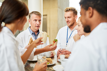 Groupe de médecins à la cafétéria ou à la cantine mangeant et se relaxant Banque d'images