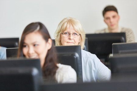 Senior woman and students in computer course at community college