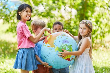 Multiculturele groep kinderen in de natuur houdt een wereldbol vast