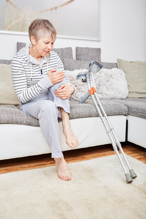 Senior woman with crutches has pain on knee