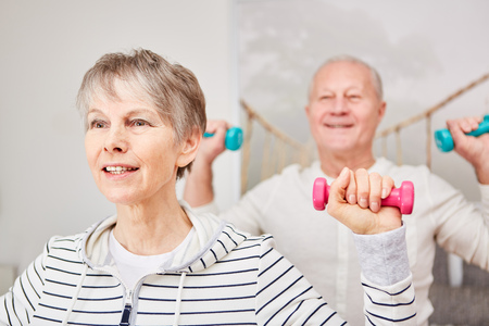 Active senior couple in fitness workout weight training class Фото со стока