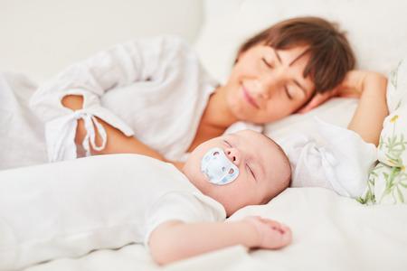 Matka i dziecko śpią spokojnie razem na łóżku w domu