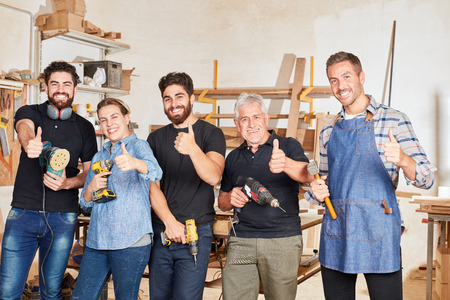 Successful carpenter team with thumbs up in the carpentry or joinery