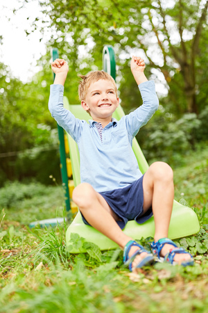 Smiling boy cheers with clenched fists on the playground in summer