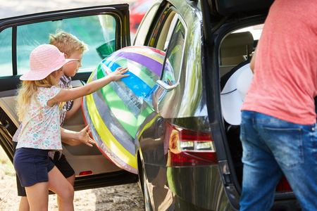 Children load a big ball in the car before going on summer vacation Stock Photo