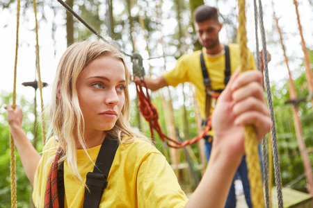 Fearful young woman struggles with vertigo on a bridge in the high ropes course