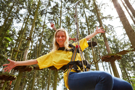 Young woman in high wire garden having fun abseiling in teambuilding workshop