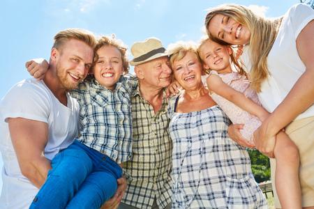 La famille élargie avec les grands-parents et les enfants rit joyeusement de la caméra