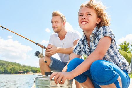 Boy fishing with his father on the lake at the weekend for relaxation