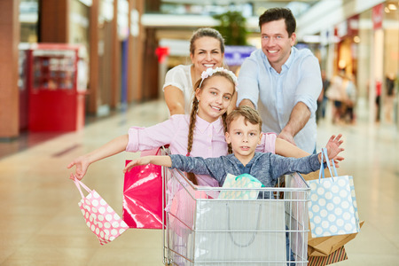 Parents and children shopping in the shopping cart have fun in the shopping center