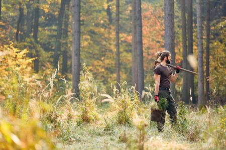 Ein junger Ranger oder Forstarbeiter pflanzt Bäume für Nachhaltigkeit und Naturschutz