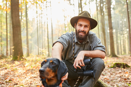 Forester with hunting dog and binoculars takes a break in his forest
