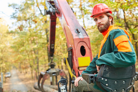 Forest farmer as a crane operator on the forwarder during logging in the wood harvest