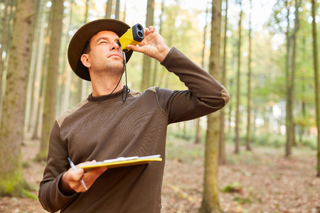 Förster uses the rangefinder to determine the tree height in forest maintenance