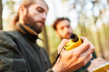 Two foresters work with the rangefinder to measure the height of the tree