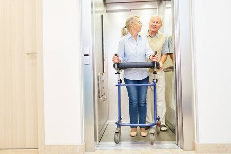 Couple of seniors with rollator in the elevator in a hospital or nursing home