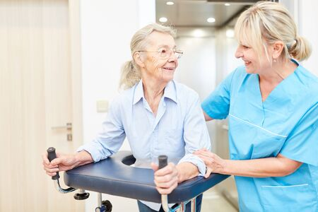 Physiotherapist and senior with rollator in the rehabilitation clinic or nursing home