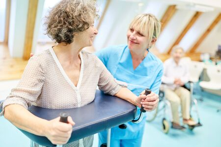 Senior woman with walker in physiotherapy is assisted by therapist Stock Photo