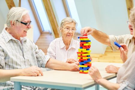 Group of demented seniors build a tower of building blocks in a therapy Stock Photo