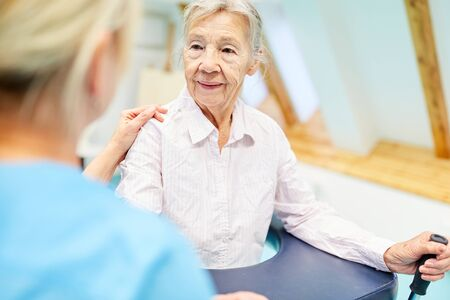 Senior woman in physiotherapy is learning to go with the help of a rehab therapist