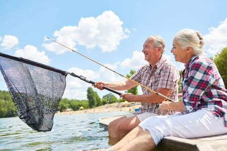 Senior couple with fishing tackle and landing net while fishing together in the summer by the lake