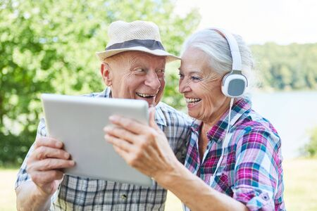 Senior couple has fun on a nature trip using tablet computer online