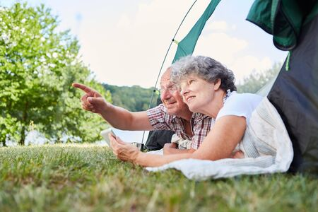 Senior couple camping in nature in tent with a tablet computer Stock Photo