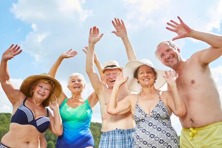 Happy seniors as friends and pensioners are going on vacation at the lake in summer Imagens