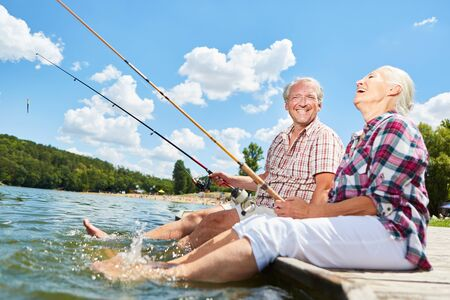Senior couple splashing with their feet in the water while fishing on the lake in summer