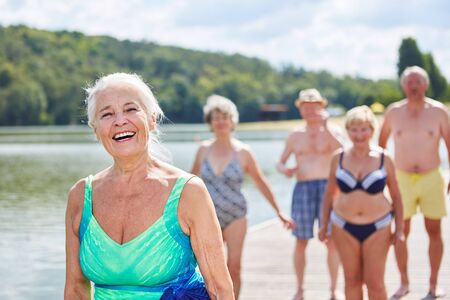 Laughing senior woman with her friends at the lake in the summer on vacation