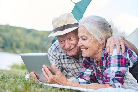 Vital senior couple camping is looking forward to an email on the tablet computer
