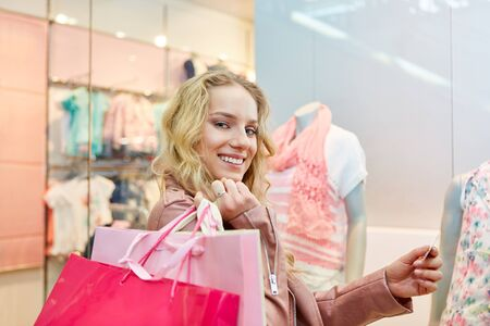 Young smiling woman with bags and with credit card while shopping