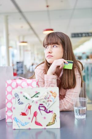 Young woman with credit card or loyalty card is bored in shopping mall