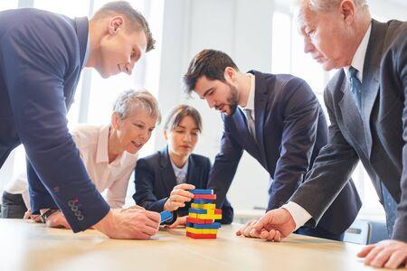 Business people make building blocks exercise in teambuilding workshop