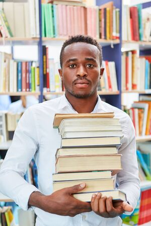 Young African as immigrant or student carries a stack of books in the library 版權商用圖片