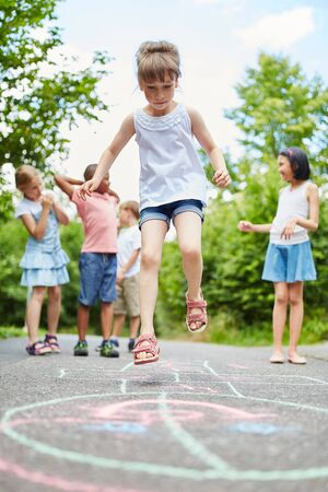 Active girl makes jump at hopscotch game with friends Stock Photo