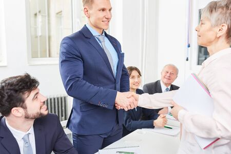 Senior businesswoman share handshake with trainee as congratulations sign