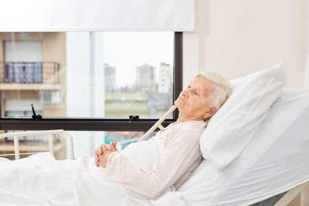Senior woman lying ill in bed in a nursing home or in the hospital