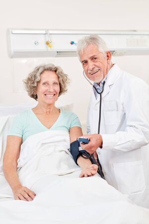 Man as head physician in blood pressure measuring at a senior citizen in the hospital Stock Photo