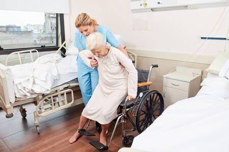 Une infirmière aide une femme âgée handicapée en fauteuil roulant dans une maison de retraite Banque d'images