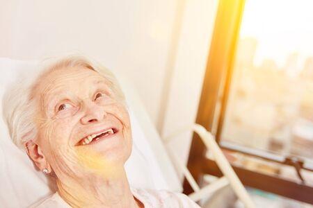 Happy senior woman is lying smiling in bed in nursing home