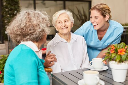 Seniors and caregivers make small talk and drink coffee at the retirement home