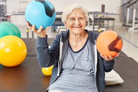 Senior woman balances balls as exercise for coordination in occupational therapy Stock Photo