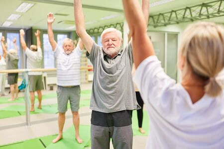 Physiotherapist as course instructor at Reha Rückengymnastik for seniors in the gym Фото со стока