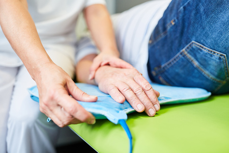 Non-medical practitioner makes magnetic therapy at the hand of a senior natural medicine Stock Photo