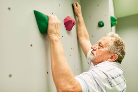 Sporty senior man climbing in a climbing gym for fitness and coordination